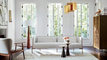 art deco apartment with white living room with brass pendant and white sofa