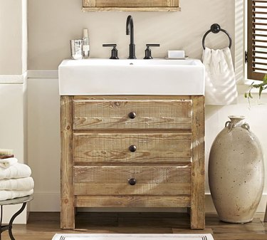 Pine country bathroom vanity with white ceramic sink in neutral bathroom