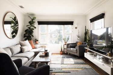 black family room window treatments in bright family room with white walls and midcentury modern coffee table
