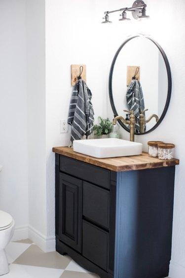 Dark minimalist bathroom vanity with circular mirror.