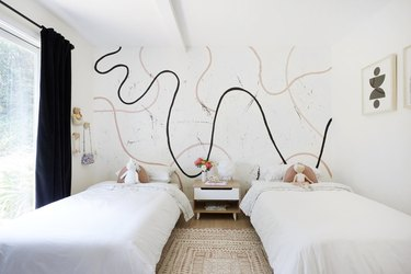 Kids' minimalist bedroom with modern mural and white bedding