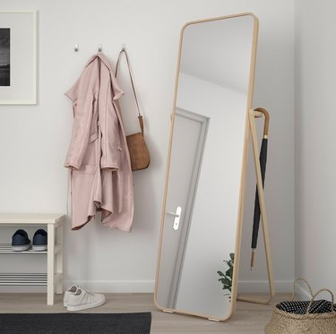 IKEA bedroom idea with a freestanding full-length mirror with a clothing rack on the back. A pink jacket and tan purse hang on wall hooks beside it