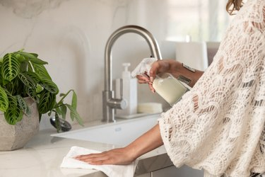 woman cleaning kitchen counter with spray and towel