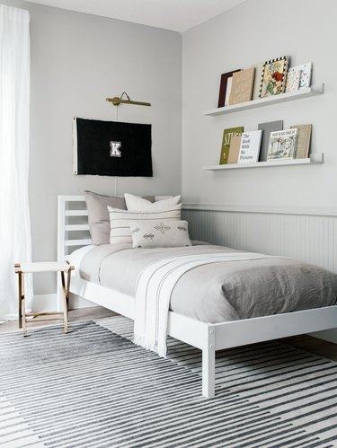 Kids' minimalist bedroom with flag decor and books on open shelving