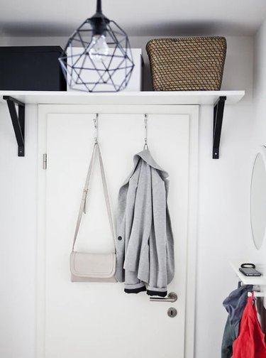 IKEA bedroom idea with a white shelf with black brackets mounted over an interior door