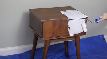 white paint being applied to wood bedside table