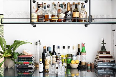 bar area with bottles, books, and plant