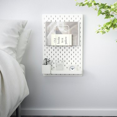 IKEA bedroom idea with a white pegboard mounted next to a bed. Pegboard has modules for glasses, water, an alarm clock, and books