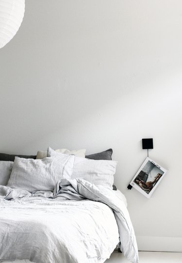 white minimalist bedroom idea with magazine hanger