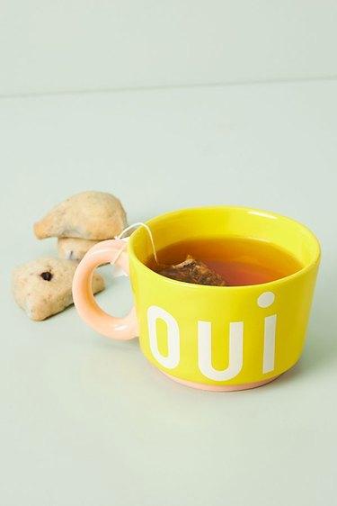 """yellow mug with """"oui"""" graphic"""