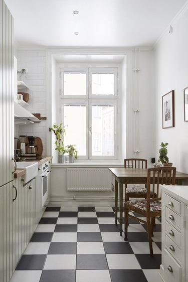 Scandinavian farmhouse kitchen with black and white checkerboard floor tile