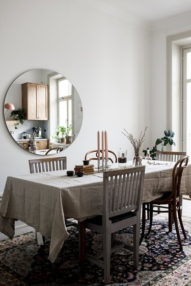 Scandinavian farmhouse style dining room with mismatched chairs and linen tablecloth