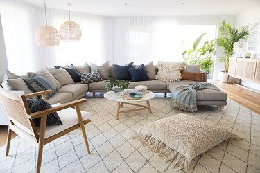 boho coastal living room with large sectional, hanging pendants