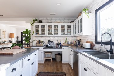 kitchen with glass-insert cabinets above and white cabinets with dark pulls below
