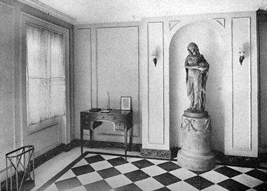 black and white photograph of space with large statue and checkered floor