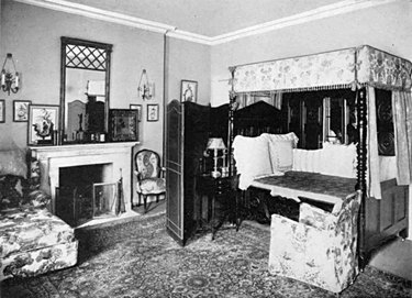black and white photograph of a bedroom space with patterned rug and chairs