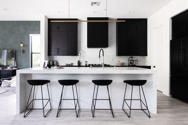 modern kitchen with white stone kitchen island, modern light fixture, black cabinets and black bar stools