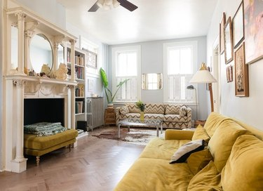 psychedelic grandma apartment with ornate fireplace and mustard yellow velvet couch