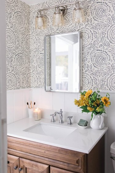 Powder room with shiplap, wallpaper, wood vanity, white counter.