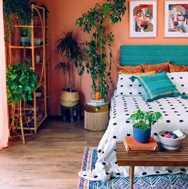 bohemian teal bedroom idea with potted plants and upholstered headboard