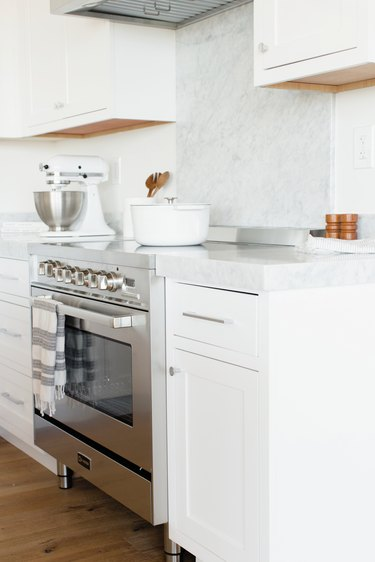 White kitchen cabinets with white marble backsplash, induction stove, mixer.