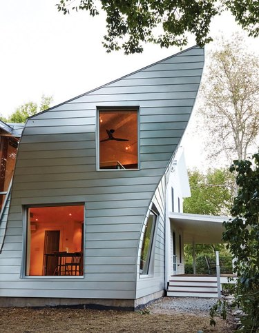 curved addition on farmhouse structure with steel siding