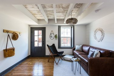 modern farmhouse living room entryway with brown leather couch and rattan pendant lamp