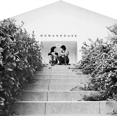 """two women sitting on steps near building with the word """"womanhouse"""" on its exterior"""