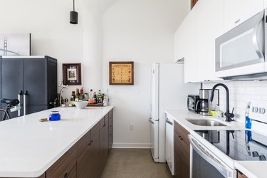 modern kitchen with white countertops and dark wood kitchen cabinets