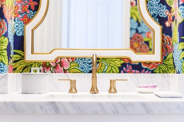 bright modern wallpaper in bathroom with marble sink and gold faucet