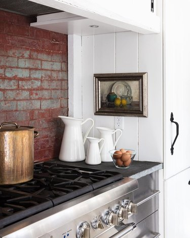 Farmhouse kitchen with red brick backsplash and slate countertops
