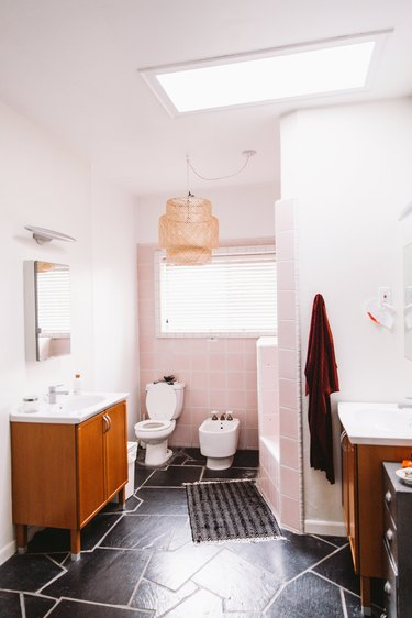 bathroom with black floor tiles, pink wall tiles, a toilet, a bidet and two sinks