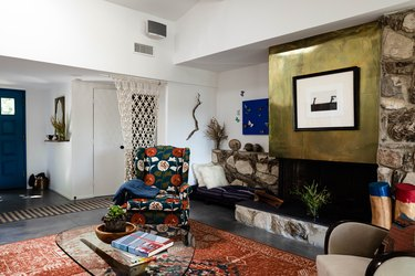 Living room with brass fireplace hood, stonework, and colorful furniture