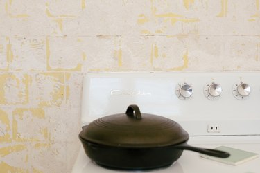 close up of electric stove and cast-iron pot with lid