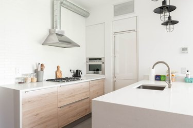 light wood kitchen and white countertops with sheperd's crook faucet spout