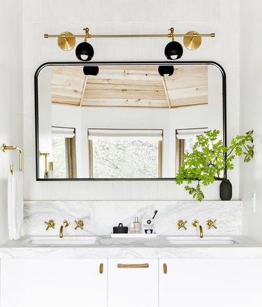Black and gold bathroom mirror lighting ideas on a gold rail in a white bathroom
