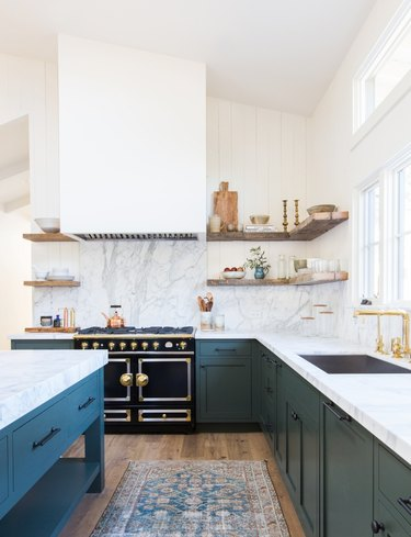 teal traditional kitchen cabinet doors in kitchen with vintage rug and floating shelves