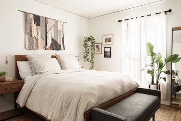 Boho bedroom with wall hanging over bed