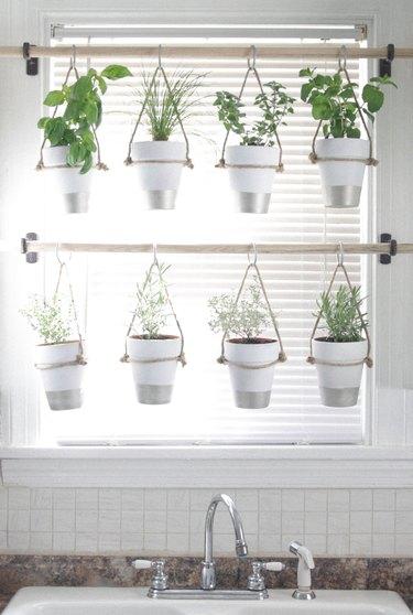 kitchen window idea with hanging herb garden on wooden curtain rods in kitchen window