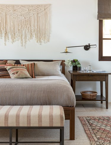 bedroom lighting ideas with yarn wall hanging and accent bench