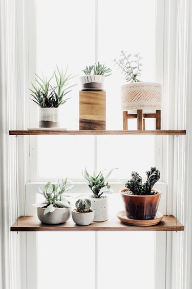 kitchen window idea with hanging shelf with wooden planks and assorted ceramic pots
