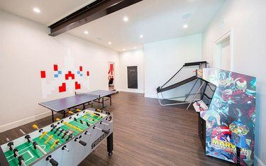 basement game room ideas in white room with light wood floors, arcade game, ping pong table, basketball game, and recessed lighting.