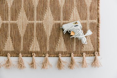 Glue the tassels along the bottom of the rug.
