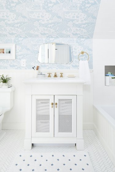 white bathroom idea with blue wallpaper on ceiling and chevron floor tile