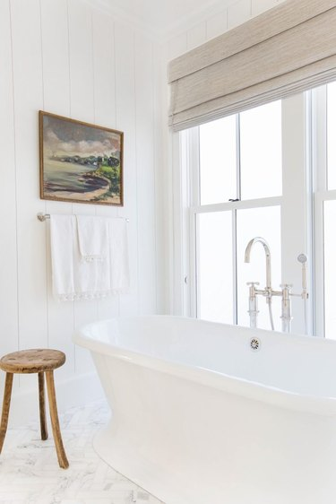 white bathroom idea with freestanding tub and Roman shade at window