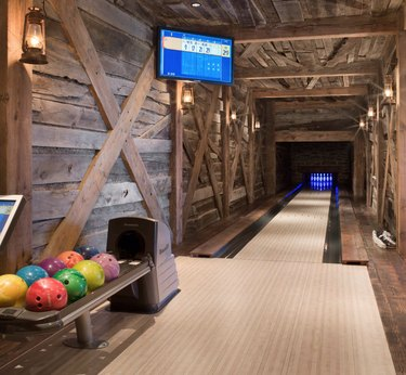 basement game room ideas with rustic wood paneled bowling lane, bowling balls, and flat screen TV