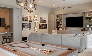 basement game room ideas with gray sectional couch, pool table, walls, flat screen tv bookshelves, pendant lights.