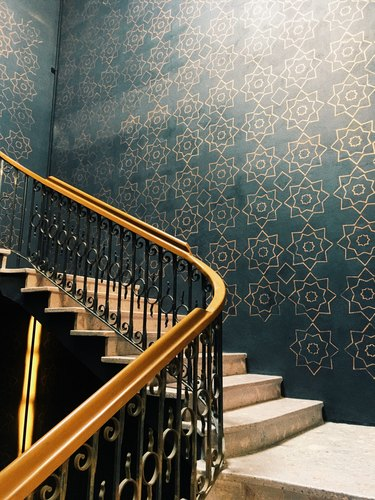 Gold and black painted stair rails with blue wallpaper.