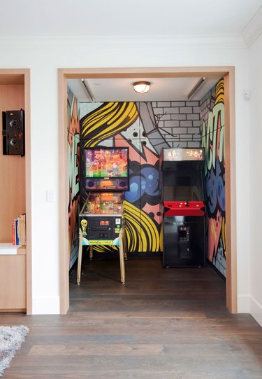 basement game room ideas with street art painted walls in nook with dome light, pinball and arcade game.