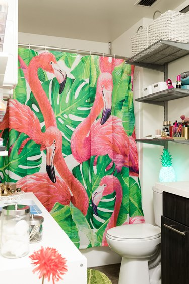 small bathroom with flamingo shower curtain, toilet, over-the-toilet storage and small bathroom vanity with sink